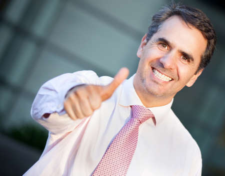 Positive businessman with thumbs up and smiling  Stock Photo - 13860509