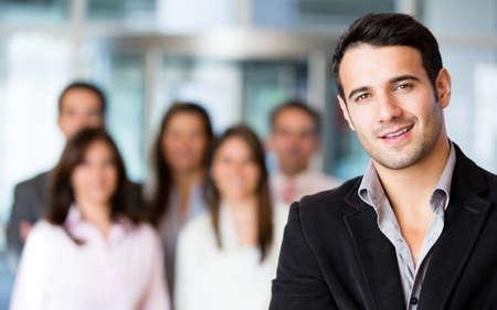 uomo felice: Uomo d'affari in ufficio con un gruppo a sfondo Archivio Fotografico