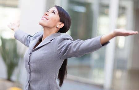 personas celebrando: Mujer de negocios exitosa con los brazos abiertos y mirando hacia arriba