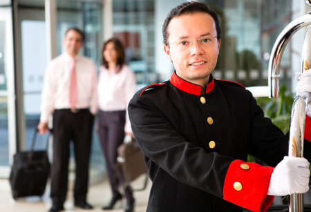 Hotel bellboy carrying the luggage of  a business couple  Stock Photo - 13877115