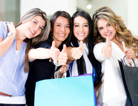 group of women: Happy shopping women with thumbs up and smiling