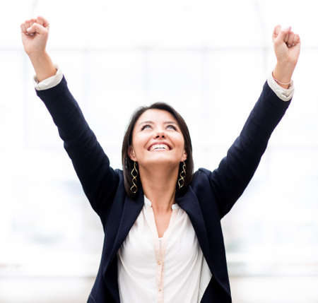 success business: Successful business woman celebrating with arms up