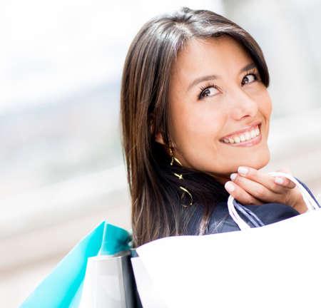 compras compulsivas: Mujer pensativa con sus bolsas de compras y sonriente Foto de archivo