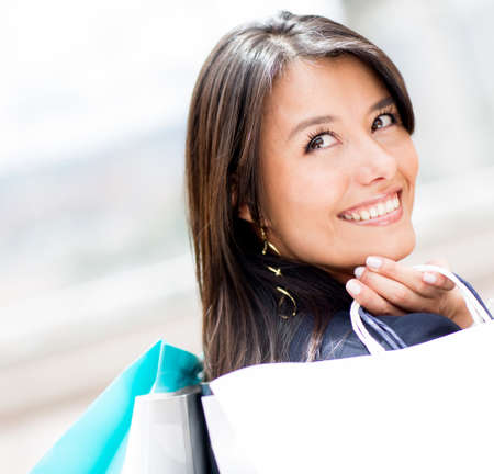 shoppingbag: Pensive woman holding shopping bags and smiling