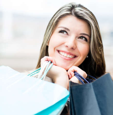 Pensive female shopper holding bags and looking up  photo