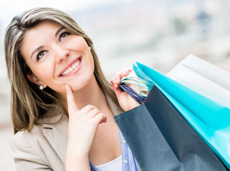 Pensive shopping woman holding bags and smiling  photo