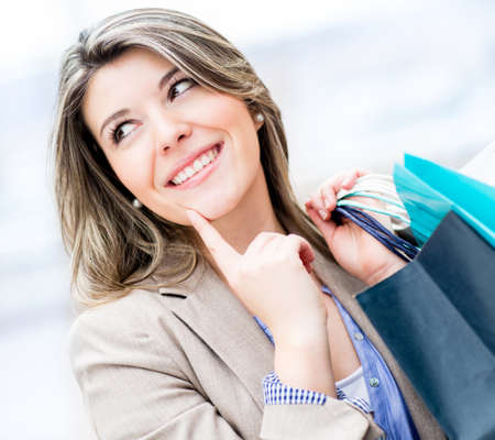 Thoughtful girl holding shopping bags and smiling photo