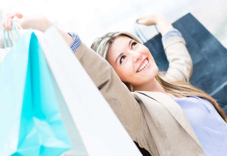 Excited shopping woman with arms up holding bags  Stock Photo - 13899545