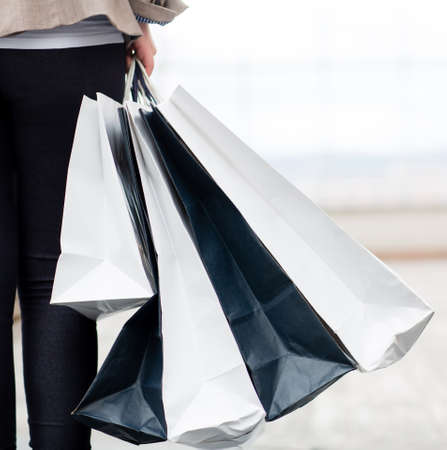 gift bags: Woman holding shopping bags at the mall while walking
