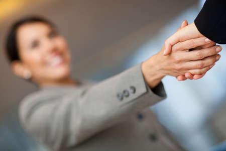 bienvenidos: Mujer de negocios de bienvenida dando un apret�n de manos y sonriendo