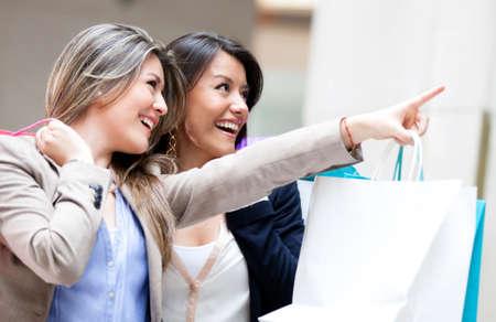 compras compulsivas: Compras mujer se�alando a la ventana y sonriendo Foto de archivo