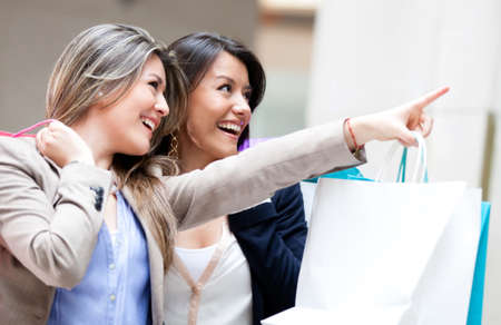 shoppers: Shopping women pointing at a window and smiling
