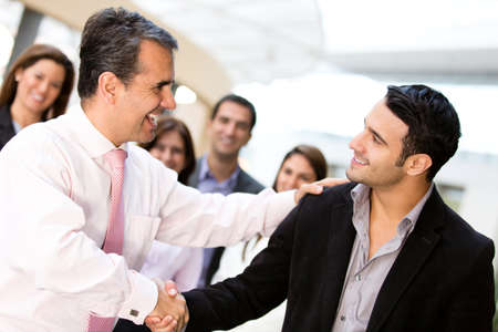 hired: Business men closing deal with a handshake  Stock Photo