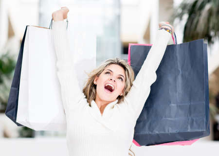 Excited shopping woman with arms up holding bags  Stock Photo - 13899541
