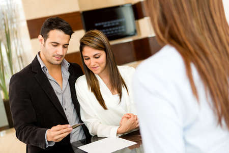 Couple doing the check-in at a hotel paying by credit card photo