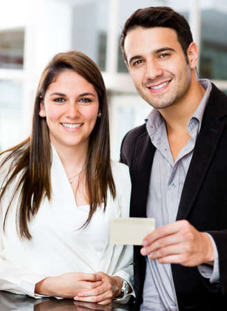 Couple holding a credit or debit card and smiling  photo
