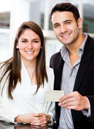 pagando: Pareja celebraci�n de una tarjeta de cr�dito o d�bito y sonriente Foto de archivo