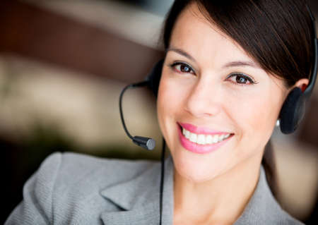 customer service representative: Friendly woman working at a call center smiling  Stock Photo