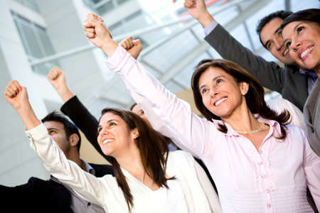 personas celebrando: Equipo de negocios exitoso con los brazos hacia arriba y sonriendo
