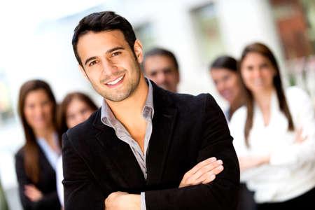 lead: Business leader maschio guardando fiducioso con un gruppo Archivio Fotografico