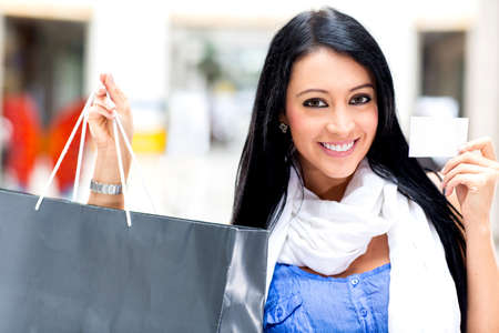 Shopping woman paying by card and holding bags  photo