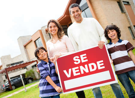 latin family: Latin family selling their house and holding a poster in spanish  Stock Photo