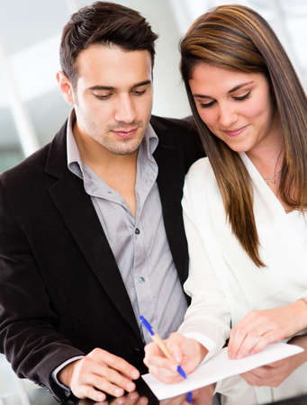 signing a contract: Successful business couple signing a document and smiling  Stock Photo