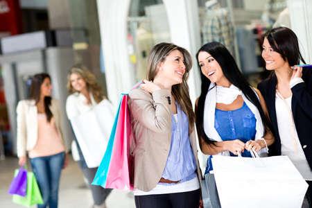 chicas comprando: Ni�as felices de compras en el centro comercial Foto de archivo