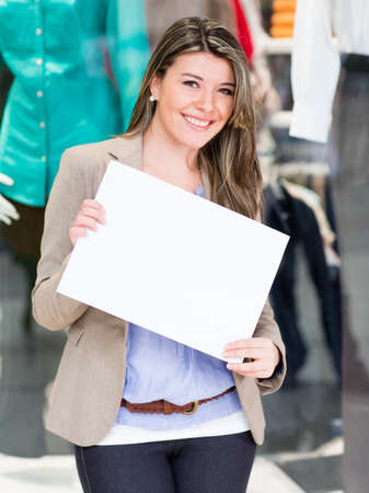 Beautiful woman holding a white banner outside a store  photo