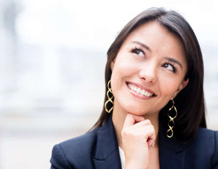 daydreaming: Pensive business woman looking up and smiling  Stock Photo