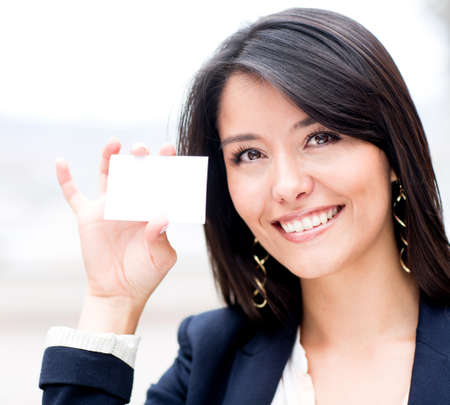 Friendly woman holding a business card and smiling  Stock Photo - 13944425