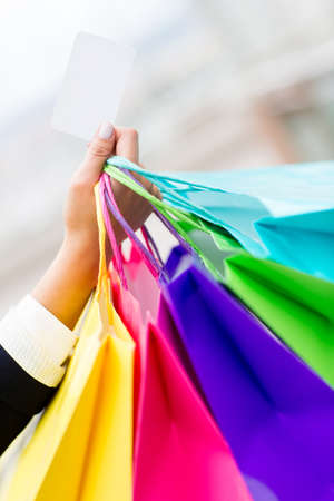 Person holding shopping bags and paying by credit card  photo