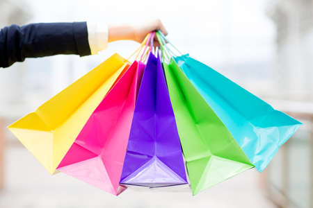 Hand holding colorful shopping bags at the mall photo