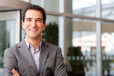 uomo felice: Felice giovane imprenditore sorridente in ufficio