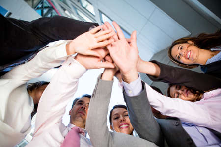 joining together: Business teamwork - group of people joining hands in the middle