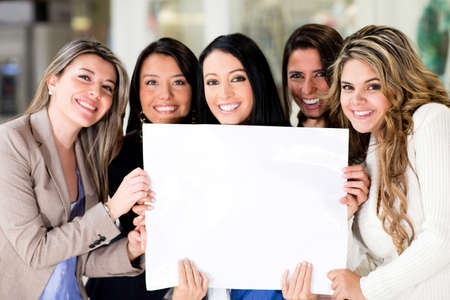 a placard: Group of women holding a banner ad and smiling  Stock Photo