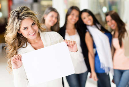 Beautiful woman holding banner with a group of girls behind  photo