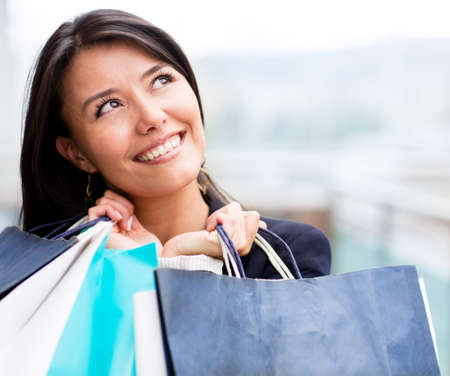 Pensive shopping woman holding bags and looking up  photo