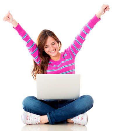 latin woman: Happy woman online on a laptop computer - isolated over white background  Stock Photo