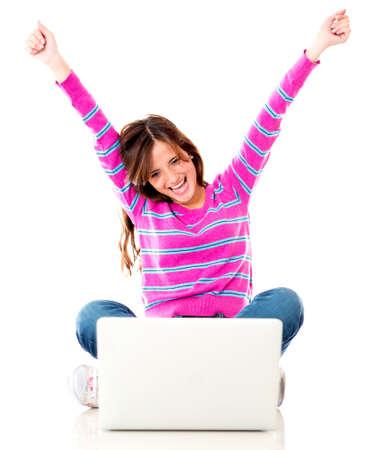 victoire: Femme excit�e avec un ordinateur portable et les bras - isol� sur blanc