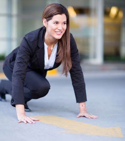 running on track: Successful business woman in position ready to race