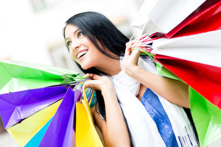 compulsive: Female shopaholic holding shopping bags and smiling  Stock Photo
