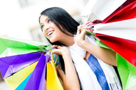 compras compulsivas: Mujer adicta a las compras con sus bolsas de compras y sonriente