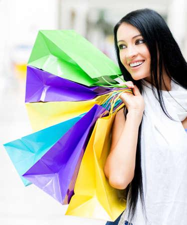 compras compulsivas: Hermosas bolsas de compras niña de la celebración en el centro comercial