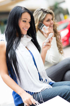 Women at the shopping center using their phones  photo