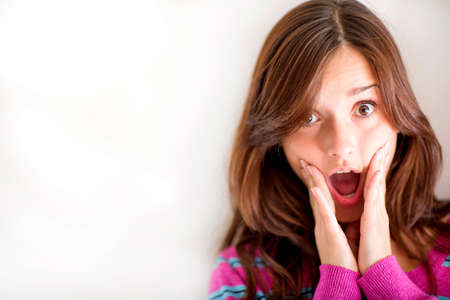 alarmed: Alarmed woman making faces - isolated over a white background
