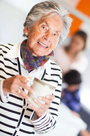 Beautiful elder woman drinking coffee at home  photo