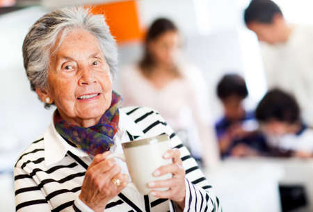 Old woman holding a cup of tea and smiling  photo