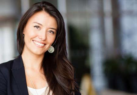 empleado de oficina: Mujer de negocios amigable sonriente en la oficina