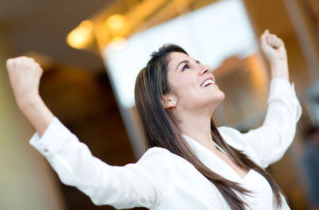 business attire: Excited businesswoman celebrating her triumph with arms up